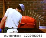 young man baking a pizza in a... | Shutterstock . vector #1202483053