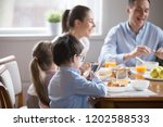while whole family eating... | Shutterstock . vector #1202588533