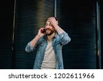 Small photo of Wondered bearded hipster guy recall important information during phone conversation with friend on smartphone device.Excited young man with stylish beard forgot to call to operator