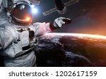 astronaut at spacewalk against... | Shutterstock . vector #1202617159