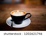 cup of hot cappucino is on the... | Shutterstock . vector #1202621746