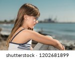 girl sitting on the coast of... | Shutterstock . vector #1202681899