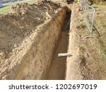 Small photo of Repairing of plastic tube water delivery system. Open trench with small diameter water pipe and heap of ground near. Excavation of trench by hand or mechanized excavator and installation.