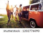friends dancing in the light of ... | Shutterstock . vector #1202776090