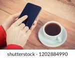 hand of woman holding smart... | Shutterstock . vector #1202884990