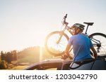 man take his bicycle from car... | Shutterstock . vector #1203042790