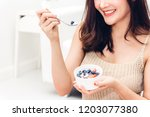 fitness woman holding yogurt... | Shutterstock . vector #1203077380