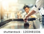 hand of man take cooking of... | Shutterstock . vector #1203481036