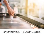 hand of man take cooking of... | Shutterstock . vector #1203482386