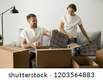 smiling young couple unpacking... | Shutterstock . vector #1203564883
