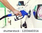 pumping gas at gas pump.... | Shutterstock . vector #1203660316