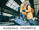 happy couple at railway station.... | Shutterstock . vector #1203860716