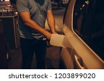 man fueling up the car in the... | Shutterstock . vector #1203899020