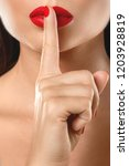 Small photo of Close-up of female lips with finger. Shush or silence gesture