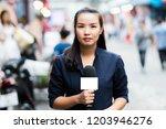 female journalist outside... | Shutterstock . vector #1203946276