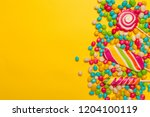 colored candies on yellow... | Shutterstock . vector #1204100119