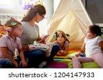 preschool teacher reading a... | Shutterstock . vector #1204147933