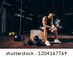 handsome athletic man sitting... | Shutterstock . vector #1204167769