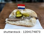 Stock photo traditional dutch snack seafood sandwich with herring onions and pickled cucumber broodje haring 1204174873