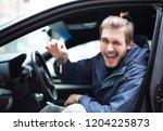 man showing keys of her new car. | Shutterstock . vector #1204225873