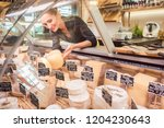 shop clerk woman sorting cheese ... | Shutterstock . vector #1204230643