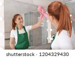 woman cleaning mirror with rag... | Shutterstock . vector #1204329430
