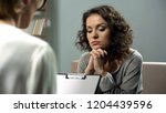 hopeless young lady listening... | Shutterstock . vector #1204439596
