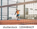 man playing padel in a orange... | Shutterstock . vector #1204484629