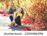 young beautiful woman on autumn ... | Shutterstock . vector #1204486396