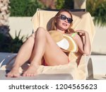 young girl relaxing on sunbed... | Shutterstock . vector #1204565623