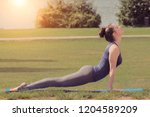 woman practicing yoga in park... | Shutterstock . vector #1204589209