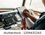 Small photo of Marine navigational officer or chief mate on navigation watch on ship or vessel. He fills up checklist. Ship routine paperwork