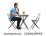 young man seated at a coffee... | Shutterstock . vector #1204638943