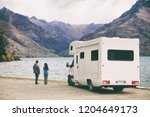 RV motorhome camper van road trip young people on New Zealand travel vacation adventure, Two tourists looking at lake and mountains on pit stop next to their rental car. - stock photo