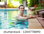 handsome man in a swimming pool ... | Shutterstock . vector #1204778890