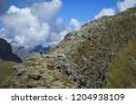 female hiker on a narrow ridge... | Shutterstock . vector #1204938109