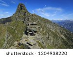 hiker on a narrow ridge in the... | Shutterstock . vector #1204938220