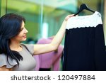 young happy woman chooses dress in clothing store - stock photo
