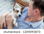 man with dog at home. adult man ... | Shutterstock . vector #1205092873
