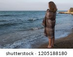 girl wrapped in a plaid stands...   Shutterstock . vector #1205188180