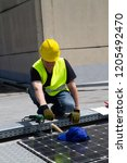 fitting photovoltaic panels on... | Shutterstock . vector #1205492470