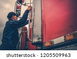 Transportation Industry Theme. Truck Driver Getting Into Truck Time To Hit the Road with Heavy Load.  - stock photo