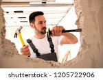 carving a hole in the wall with ... | Shutterstock . vector #1205722906