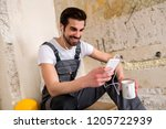 smiling young worker enjoying... | Shutterstock . vector #1205722939