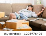 Stock photo tired businessman in the office after work with dollars money and stack of carton boxes 1205976406