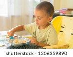 the boy 2 years eats porridge.... | Shutterstock . vector #1206359890