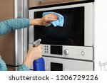 woman cleaning oven with rag in ... | Shutterstock . vector #1206729226