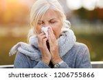 sick woman blowing her nose  | Shutterstock . vector #1206755866