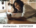 woman using a smartphone at... | Shutterstock . vector #1207072039