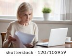 serious aged woman holding... | Shutterstock . vector #1207103959